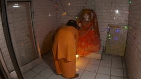 Hindu monk performs night religious ritual aarti with fire in front of statue of Goddess flashlights