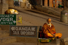 Hindu Monk at Varanasi. Hindu men in religious contemplation on the steps of the Hindu Ghats near the Holy River Ganges in Varanasi in northern India. The river Stock Photo