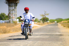 Hindu old man on a motorbike. Old man on a motorbike riding at the village in Nagaur district Royalty Free Stock Photography
