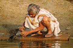 Hindu Pilgrim cleaning prayer utensil Stock Photos