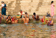 Hindu pilgrims in Benares. VARANASI, INDIA - APRIL 1: Unidentified Hindu pilgrims take bath and pray in the holy water of Ganges river on the auspicious Stock Photo