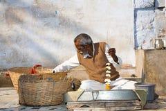 Hindu preparing floral garlands Stock Images