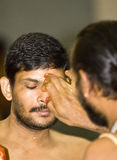 Hindu priest places a mark on the forehead Stock Photography