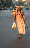 Hindu priest walking down busy street, India. Stock Photos