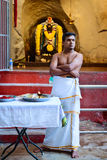 Hindu priests in Batu caves temple. KUALA LUMPUR, MALAYSIA - 22 MAR 2017: Hindu priests in Batu caves temple with the God statue on background royalty free stock images