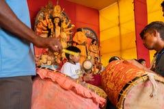 Hindu priests feeding Goddess Durga -. KOLKATA, INDIA-SEPTEMBER 27,2017: Dhaakis drummers performing while hindu brahmin priests feeding Goddess Durga covered stock photo