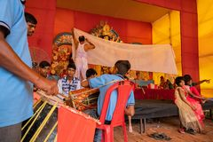 Hindu priests feeding Goddess Durga -. KOLKATA, INDIA-SEPTEMBER 27,2017: Dhaakis drummers performing while hindu brahmin priests feeding Goddess Durga covered royalty free stock photo
