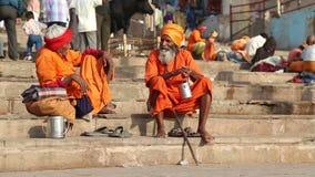 Hindu priests sitting on ghats of Ganges in Varanasi. VARANASI, INDIA - 22 FEBRUARY 2015: Hindu priests sitting on ghats of Ganges in Varanasi stock footage