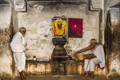 Hindu Priests. Two Hindu priests tending one of the shrines at the temple in Melkote - Southern India royalty free stock photo