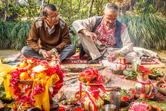 Hindu Priests with worshiping stuffs. Hindu priests with flowers and other worshiping stuffs on the Yard of house in Chitwan,Nepal Stock Images