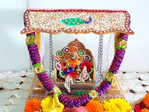 Hindu religion. Small idol of hindu god lord Krishna sitting on a swing is worshipped in celebration of his birth anniversary Stock Photography