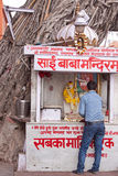 Hindu Shrine and Devotee. JAIPUR, INDIA - MARCH 26, 2014: An unidentified man makes an offering at a Hindu shrine in the lee of a banyan tree at the side of the Royalty Free Stock Photo