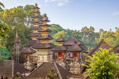 Hindu stone temples with tall pagodas in the jungle. Hindu temples in the jungle made by stone. The gilt pagodas are reflecting the early morning sunshine, Ubud stock photos