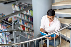 Hindu student boy or man reading book at library Royalty Free Stock Images