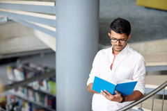 Hindu student boy or man reading book at library Royalty Free Stock Photo