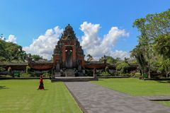A woman walking by Hindu Taman Ayun Temple in Bali indonesia royalty free stock photography