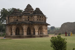 Hindu Temple, Hampi, India. Hindu temple at the archaeological complex of the ruins of Hampi, India. Temple surrounded by green garden with people stock image