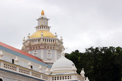Hindu temple shrine dome. A Hindu temple dome over the shrine. Beautifully decorated with carvings and made of pure white marble. An overcast sky in the Royalty Free Stock Photos