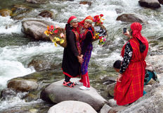 Young women in colorful clothes on a river bank wi Royalty Free Stock Photo