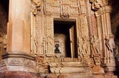 Hinduisk gud i mörker av den forntida templet av Khajuraho, med sned stenväggar, Indien Lokal för Unesco-världsarv Royaltyfria Bilder