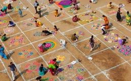 Hinduisk kvinnaattraktionrangoli med kulöra pulver, blommor i pongal eller makarasankrantifestiva royaltyfria foton