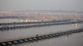 Hinduiska fantaster som korsar pontonbroarna över Gangeset River på den Maha Kumbh Mela festivalen royaltyfri fotografi