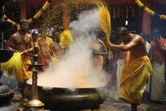 Hinduiska fantaster utför gurkmejabadningritualen under den årliga festivalen som rymms på den Amman templet royaltyfri fotografi