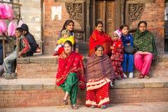 Hinduiska kvinnor i traditionell sari sitter på den gamla Durbar fyrkanten Störst stad av Nepal, dess kulturella mitt Royaltyfri Bild