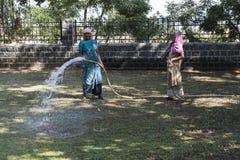 Hinduiska kvinnor som arbetar bevattna en trädgård Royaltyfri Foto