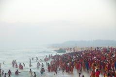Hinduiskt folk, grupp i rött på havet i Tamil Nadu, Indien Royaltyfri Fotografi