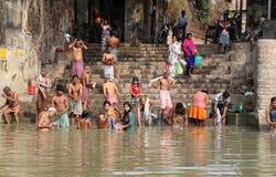 Hinduiskt folk som badar i ghaten nära Dakshineswaren Kali Temple i Kolkata Arkivfoto
