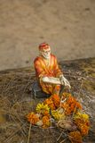 A hinduism ancient statuette of the holy man Sai Baba with offerings on blurred background. Hinduism ancient statuette of the holy man Sai Baba with offerings on stock image