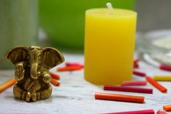 Hinduism god Ganesh statuette on grey table with yellow candle and colorful sticks. Spa table background. Spa design and decoration Stock Photography