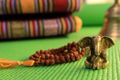Hinduism god statuette Ganesh on green yoga mat with unfocused rudraksha beads and yoga pillow and bell. Modern sport. Spiritual b. Ackground. Yoga background Stock Photo