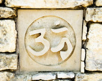 Hinduism's Om symbol. Ceramic tile in old rock wall with the om sign, a religious symbol representing hinduism.  Tile is one of a series of seven representing Royalty Free Stock Photos