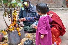 Un bambino e la sua madre sta pregando Immagine Stock