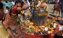 Hindus realiza Puja a la estatua de la piedra de señor Shiva, cerca del templo, en Mahasihvaratri fesival Fotos de archivo libres de regalías