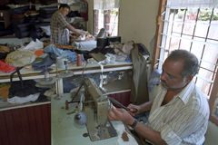 Hindustani tailor working in Dressmaking, Surinam. Suriname, capital, city Paramaribo: two men working as a tailor. The one state to iron a garment, and the royalty free stock image