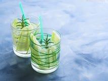 Hineingegossenes Wasser mit Gurke und Rosmarin Stockfotografie