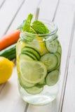 Hineingegossenes Wasser mit Zitrone, Gurke und Minze Lizenzfreie Stockbilder