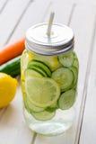 Hineingegossenes Wasser mit Zitrone, Gurke und Minze Stockfotos