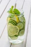 Hineingegossenes Wasser mit Zitrone, Gurke und Minze Lizenzfreies Stockfoto