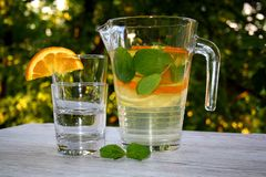 Hineingegossenes Wasser mit Zitrusfrüchten und Minze stockbild