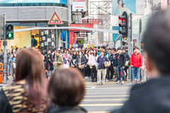 Hing Kong. HONG KONG, HK - FEBRUARY 12, 2015: Pedestrians crossing a street in Hong Kong..There are more than 35 million of visitors arrived Hong Kong from Royalty Free Stock Image