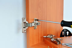 Hinge assembly on kitchen cabinet Royalty Free Stock Images