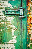 Hinge on rusty metal door with cracked paint Stock Images