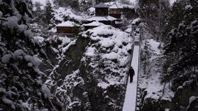 Hinged bridge leading to the temple of a mountain river. Man goes. Mountain river Katun, Altay, Russia. A winter scenic on Chemal stock footage