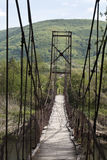 Hinged bridge over mountain river Stock Image