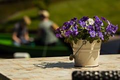 Hink av blommor med två personer i ett fartyg i den suddiga backgen Royaltyfri Foto