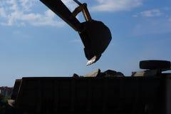 hink av grävskopan som bär skriven jordning till lastbilkroppen royaltyfri foto